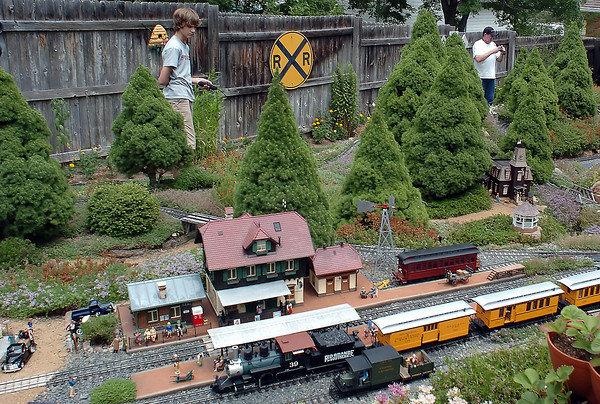 Jackson Buckner, 14, left, uses a remote control to operate a large-scale model train Saturday in the backyard railroad of his grandparents, Ed and Celia Frey, not pictured, as Steve Gage of Ozark, Ark. takes pictures of the layout during the Garden Railroads on Tour event. Members of the Northern Colorado Garden Railroaders accepted cash and non-perishable food donations to tour their garden railroads with all cash and food collected going to House of Neighborly Service and Food Bank for Larimer County.