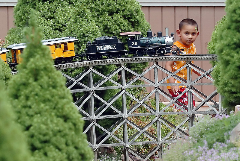 Three-year-old Isaiah Laney watches as a model train makes its way over a trestle Saturday afternoon in the garden railroad of Loveland residents Ed and Celia Frey during the Garden Railroads on Tour event. Members of the Northern Colorado Garden Railroaders accepted cash and non-perishable food donations to tour their garden railroads with all cash and food collected going to House of Neighborly Service and Food Bank for Larimer County.