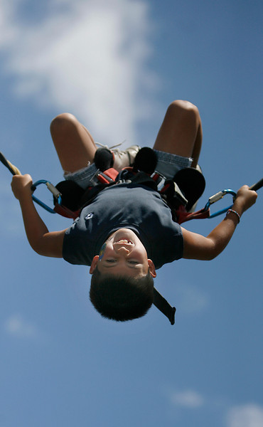 Loveland resident Jadyn Tafoya, 7, does a back flip on the Bungee-Tramp during the SummerFest Sunday at Loveland Civic Center Park.