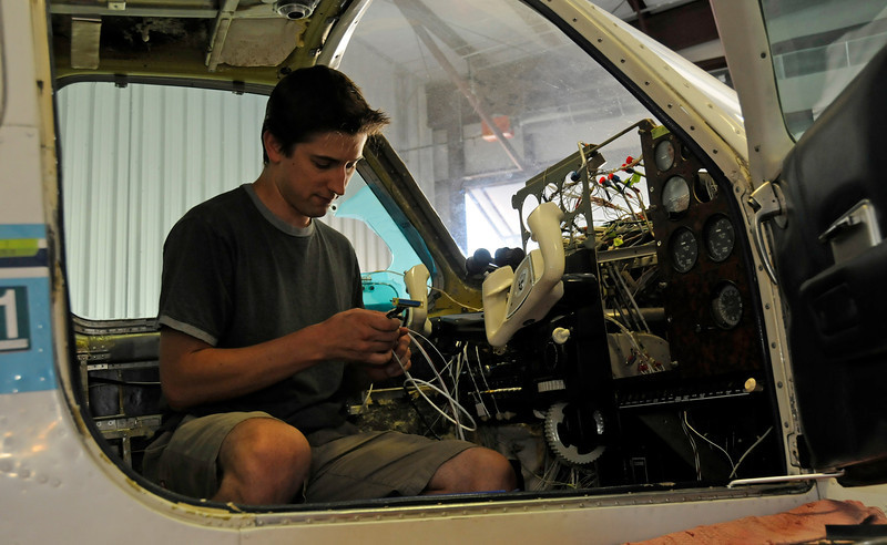 Chris Kregoski works on the autopilot of an airplane being refit with new equipment at Avionics Specialists near the Fort Collins-Loveland Airport. Avionics Specialist works with planes and weather cameras, which they are expanding to help pilots get more accurate weather information before they take off.