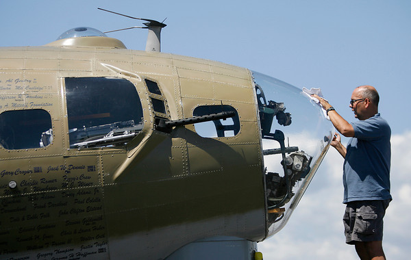 Steve Arnold, flight engineer, cleans the bugs off the front glass of a B-17 bomber during the Wings of Freedom Tour at the Loveland Airport.