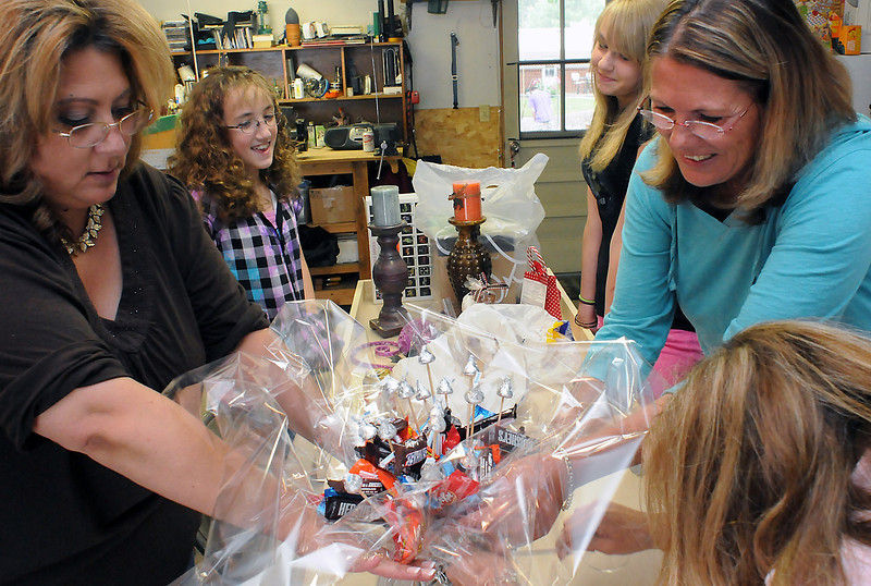Volunteers decorate a gift container filled with candy Wednesday evening that will be one of the prizes available for participants in the upcoming Katie's Ride poker run and auction on July 18. Clockwise from left are Conni MacDonald, Katie Thiede, Hailey Boone, 12, Becky Phetteplace and Kris Boone.