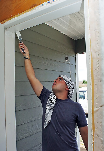 Saif, 19, paints around the front door of a home being built in Loveland, Colo. for Habitat for Humainty while volunteering with other college students from Iraq visiting the United States through the World Learning program on July 17, 2010.