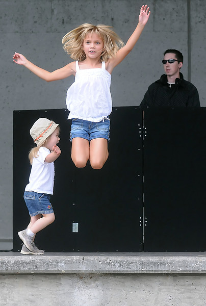 Eight-year-old Maya Maes-Johnson leaps off the Hammond Amphitheater stage while dancing with Emily Noble, 2, and other children Saturday to music being spun by DJ Neal Johnson with Loveland-based JP Entertainment.