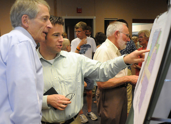 Evan Patterson, left, and his nephew, Jon-Mark Patterson, look over plans for the Loveland Public Library's expansion and renovation Thursday during a reception in the Gertrude Scott Room after an earlier groundbreaking ceremony outside the library.
