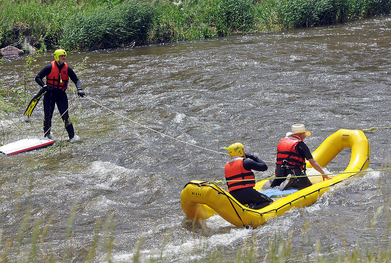 A fisherman, right, is assisted to shore by dive rescue team members from the Loveland Fire and Rescue Department after becoming stranded by rushing waters while wading in the Big Thompson River on Friday afternoon upstream from the Idylwilde Dam.