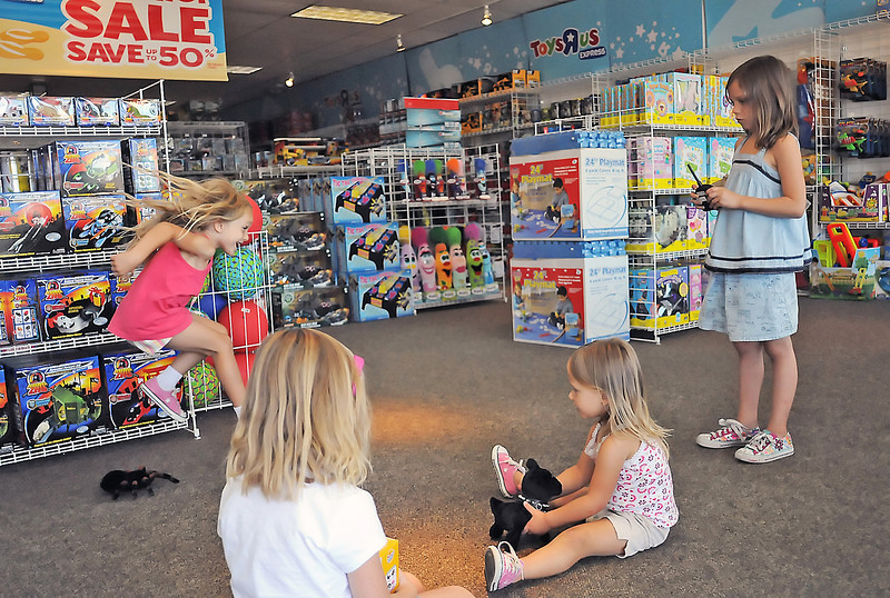 Five-year-old Kylie Baumert, back left, leaps over a remote-controlled electronic spider while checking out toys Friday with, front from left, Jossyln Rogers, 6, Kaydian Baumert, 2, and Jori Rogers, 8, at the newly-opened Toys R Us Express, 5967 McWhinney Blvd., at the Outlets at Loveland. The store's hours are Monday through Saturday from 10 a.m. to 8 p.m. and Sundays from 11 a.m. to 6 p.m. For more information call, 635-3046.