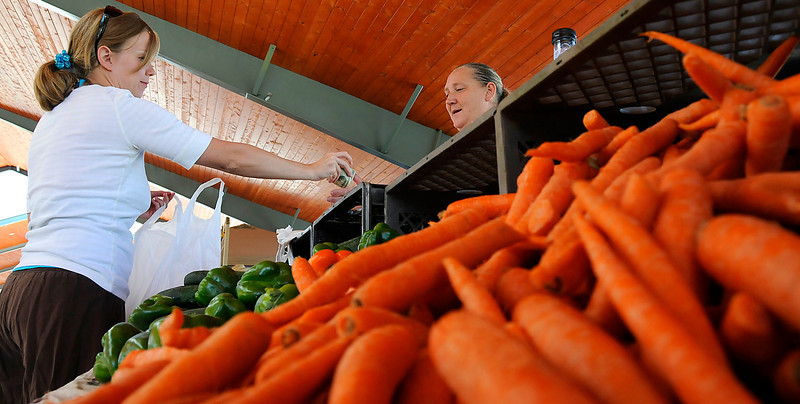 Loveland resident Robin Ramsey, left, buys some produce from Edna Troutman of Miller Farms during the Farmers' Market at Fairgrounds Park on Sunday. The market takes place on Sundays from 11:00 a.m. till 3:30 p.m. at the Fairgrounds Park on 700 S. Railroad Avenue.