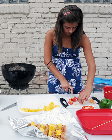 Loveland resident Annie Vreeman, 10, slices peppers as she prepares a citrus chicken with pineapple dish Friday during the Loveland Loves Barbecue Kids Q competition.