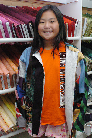 Mia Roberts, 10, models a jacket that she was working on Wednesday at the Sweetheart Quilt Shoppe in preparation for the upcoming 4H recycled clothing project competition at the Larimer County Fair. The jacket includes a variety of different patterns from men's ties sewn onto a sweatshirt using the crazy quilting technique.