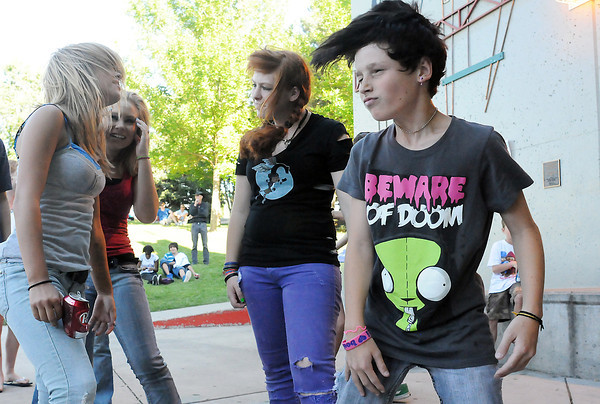 "Teens dance in front of the stage at the Hammond Amphitheater while the band ""Social Outcast"" performs during the Battle of the Bands on Wednesday. From left are Melissa Johnson, 14, Terra Harden, 16, Sadie Adams, 16, and Noah Cross, 13."
