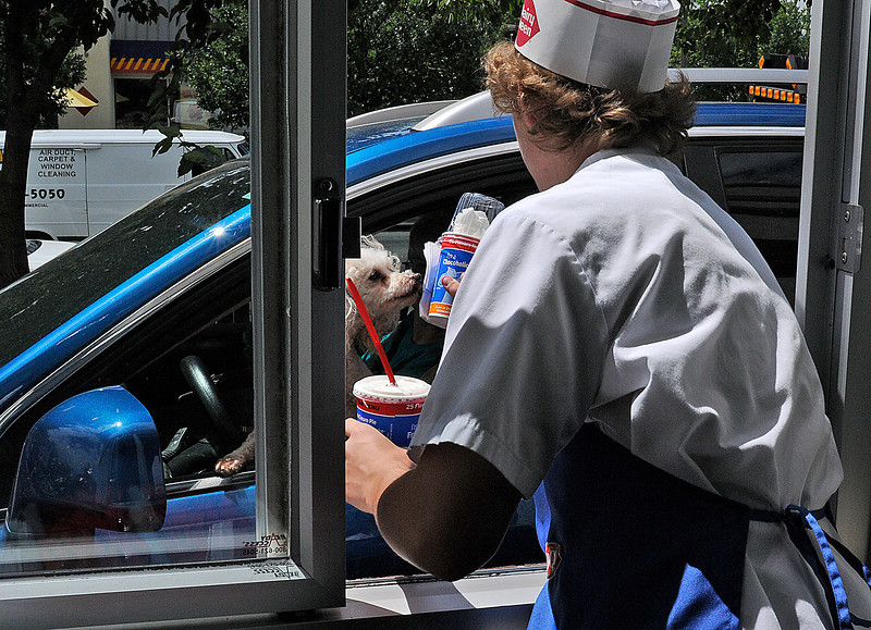 Loveland resident Derik Lints, 16, hands out some ice cream to an eager costumer at the Dairy Queen on the corner of Eisenhower Boulevard and Lincoln Avenue. Derik was busy all day with temperatures reaching 96 degrees in Loveland on Tuesday.