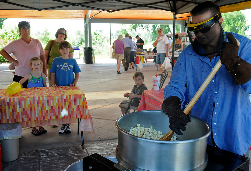 Loveland resident Cat Ryden mixes up some fresh popped kettle corn while costumers wait for the next batch during the Farmers' Market on Sunday at the Fairground Park on 700 S. Railroad Avenue. Cat is constantly mixing and cooling the kettle corn to keep her costumers full.
