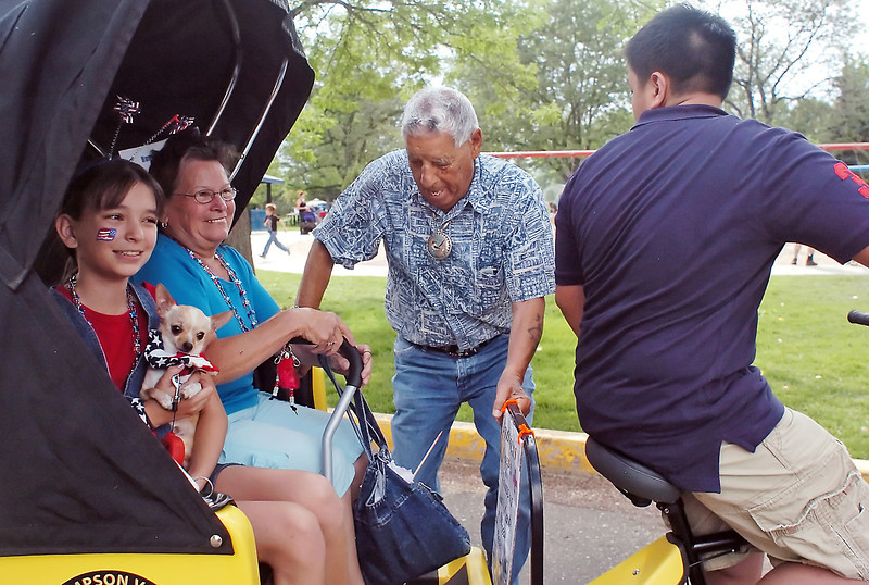 At left Longmont resident Donicca Lopez, 13, holds her Chihuahua named Nikota as she prepares to take a ride with her grandparents, Rosalita and Cris Lopez, in a pedal cab driven by Kevin Ha, 16, on Sunday at North Lake Park in Loveland.