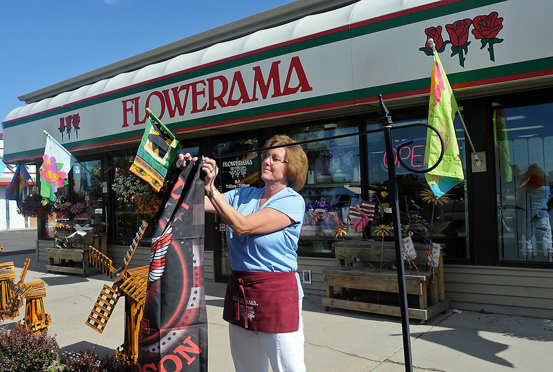 Flowerama owner Sabrina Covalt installs Friday one of the flags she has available for purchase at her flower store located at 1300 E. Eisenhower Blvd. on the southeast corner of the intersection of Eisenhower Bouldevard and Madison Avenue.