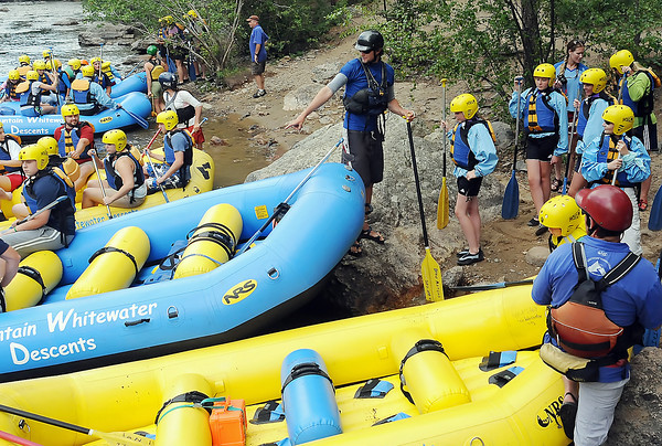 Rafters prepare to take a trip with Mountain Whitewater Descents down the Poudre River northwest of Fort Collins on Wednesday, July 21, 2010 as river guide Drew Mangus, center, loads paddlers into his boat.