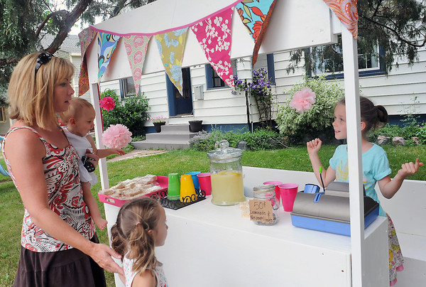 Six-year-old Ryland Nelson, right, helps customers Friday afternoon at her lemonade stand outside her home in downtown Loveland. From left are Cindy Siebert, Mia Siebert, 1, and Emma Siebert, 5, who purchased honey-ginger lemonade as well as Rice Krispies treats. Ryland said she was donating the proceeds from her stand to a neighbor to help with their medical care.