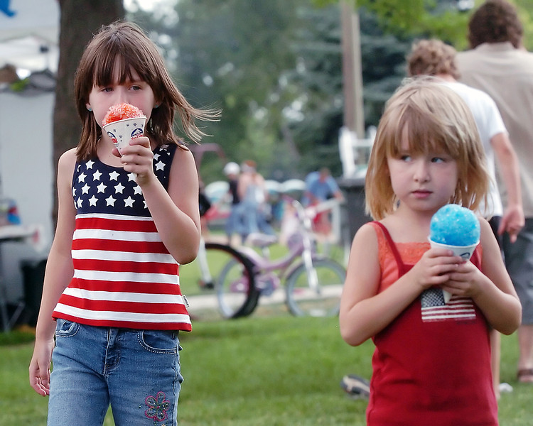 Mikaylis Martin, 7, left, and her sister, Peyton Martin, 6, eat sno-cones while spending the day with their parents at North Lake Park on Sunday.