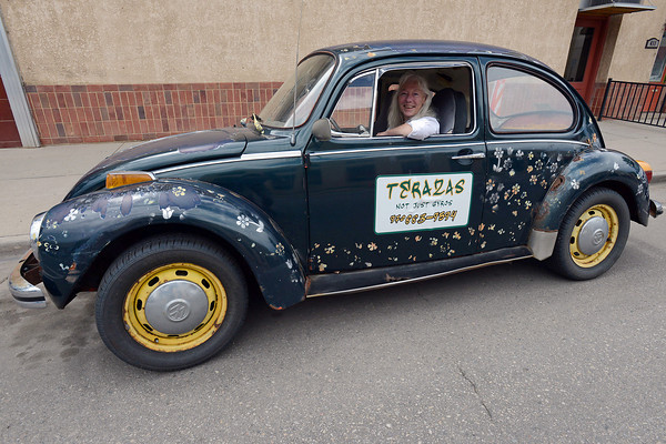 Terazas Not Just Gyros owner Terry Madigan poses Friday in her 1973 Super Beetle that's decorated with hand-painted flowers and a sign for her restaurant.