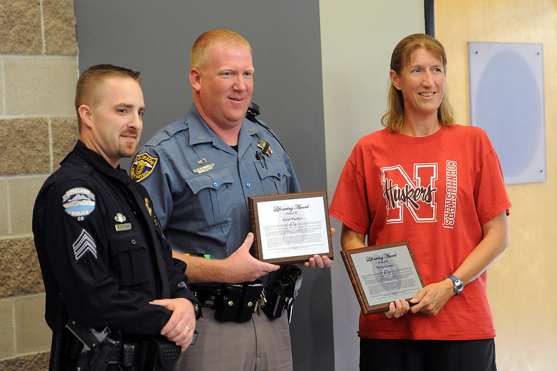 Loveland Police Sgt. Ryan Ertman, left, stands with Life Saving Award recipients Scott Pucket, a trooper with the Colorado State Patrol, and Cherie Circenis after presenting plaques to them during a ceremony at the CSP's Larimer County office on Wednesday, July 25, 2012.