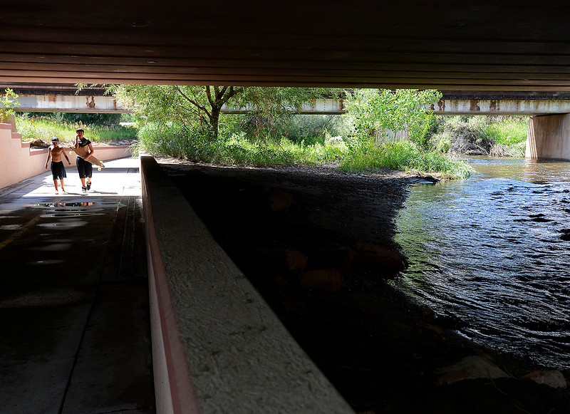 Water runs high in the Big Thompson River Monday after a few days of heavy rain as Drew Delaney, 13, left, and Anthony Manzanares, 13, walk along the Recreation Trail under Railroad Avenue Monday in Loveland.