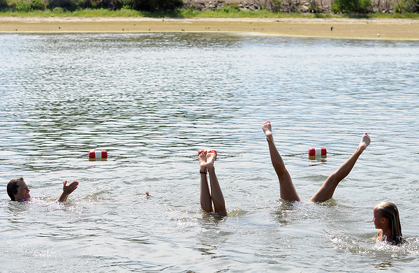 Audra Foust, left, claps as Nyah Gettman, 14, center left, and Braydee Foust, 15, do handstands in the water in Lake Loveland at the swim beach Friday. Kenzie Linneman, 9, right, also watches.