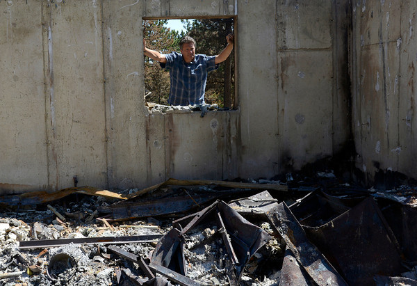Mark Squibb looks into what used to be his family's walkout basement on their property off Davis Ranch Road.