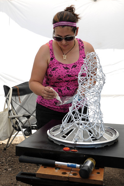 Loveland-based artist Kerri Ertman puts together a sculpture with found objects during the Welded Art and Assemblage Show outside the Loveland Feed and Grain on Saturday, July 14, 2012.