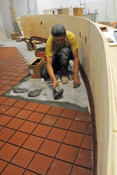 Peng Wang lays tile Wednesday inside the new Kobe Sushi restaurant, which is scheduled to open next month in the Marketpalce at Centerra in east Loveland. (Photo by Craig Young)