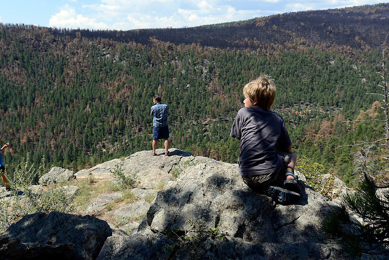 Mark Squibb and his son Hunter, 8, look at the view showing some of the blackened forest after the High Park fire from one of their favorite spots on their property.