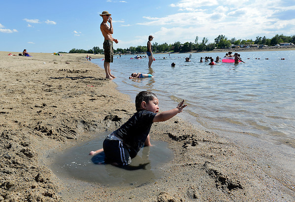 Angel Godoy of Loveland, 14 months, plays in the water and sand Friday at the swim Beach at Lake Loveland.