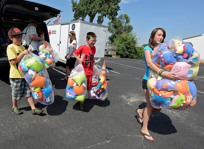 "Tollison twins Ben, 10, left, and Sam, 10, center, and their sister Zoie Tollison, 14, deliver 225 stuffed monsters to the American Red Cross office in Fort Collins on Friday afternoon. Their parents Ray Tollison and Sarah Fox help unload the toys. The boys, who design the monsters, wanted to make sure children affected by the High Park fire had a new toy after the disaster. Over 100 northern Colorado and Denver community members volunteered time to help sew the monsters. The boys usually donate one monster to a charity that helps children for every one they sell but in this case they donated hundreds before selling. Ben Tollison said he wanted to give the monsters to the children to ""give them a smile."" Sarah fox added that the main ingredient in every monster is love. For more information about the monsters check out their website at amonstertolove.com."