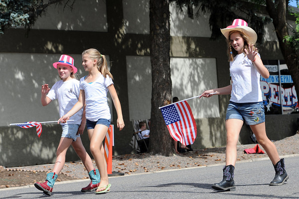 Silver Spurs 4-H Club members Samantha McCrimmon, 10, left, Alayna McCrimmon, 12, and Hailie McCrimmon, 12, walk together during the Larimer County Fair Parade in downtown Loveland on Saturday, July 28, 2012.