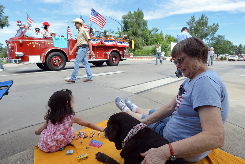 Twenty-month-old Serena Shannon sorts her candy while watching the Larimer County Fair Parade with Carol Christensen and her dog Conchita on Saturday, July 28, 2012 in downtown Loveland.