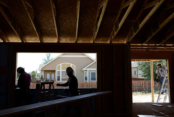 Construction employees Javier Ochoa, left, Joel Hernandez, center, and Jose Santos work on a home Monday afternoon in the Kendall Brook subdivision in Loveland.