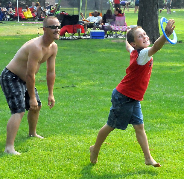 Josh Davis and 7-year-old Ty Diesing play with a flying disc Wednesday afternoon while hanging out with friends and family members at Loveland's North Lake Park.