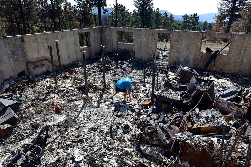 Dakota Squibb, 11,  looks through the remains of his family's home off Davis Ranch Road.