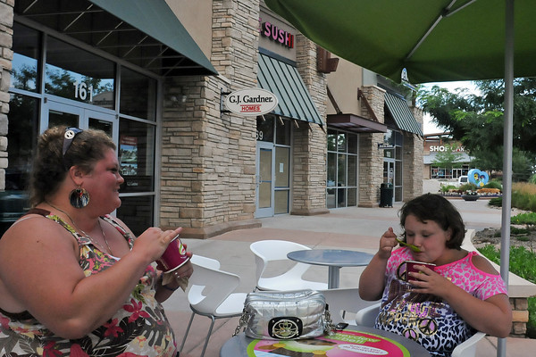 Loveland resident Amber Tilton and her 9-year-old daughter, Aislinn, enjoy some frozen yogurt Wednesday outside the Menchie's shop in the Marketplace at Centerra. Behind them, work progresses inside the new Kobe Sushi restaurant that is scheduled to open in August. (Photo by Craig Young)