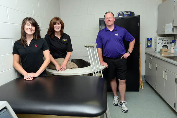 Loveland High School athletic  trainer Jessica Metcalf, left, Thompson Valley's Lindsey Jacobson and Mountain View's Nick Frei pose together in the athletic training room at Mountain View on Tuesday, July 3, 2012.