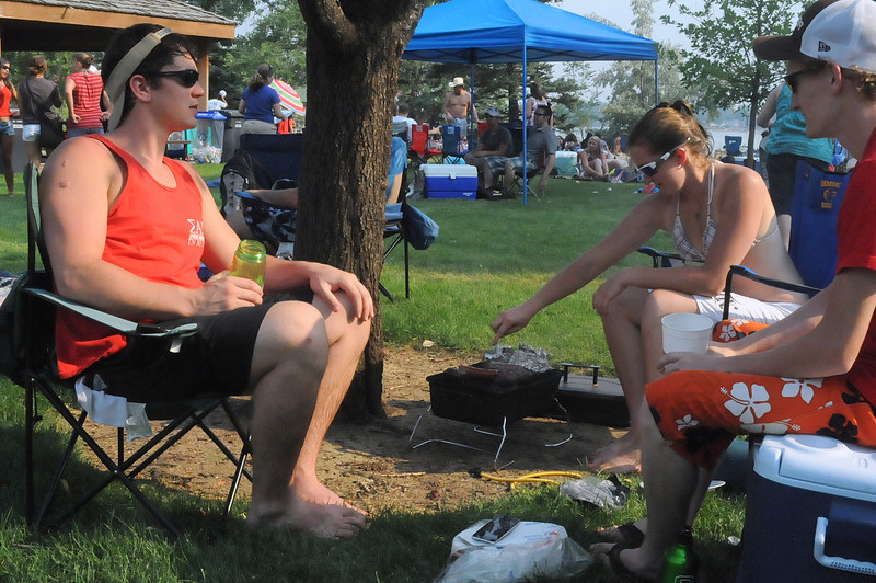 Jacob Pitts, left, Margaret Gruca and Jared Hannig enjoy the shade of a tree near Lake Loveland in North Lake Park while Gruca tends to the barbecue grill. The friends, all Fort Collins residents, were hanging out at the park Wednesday afternoon before the Fourth of July fireworks show.