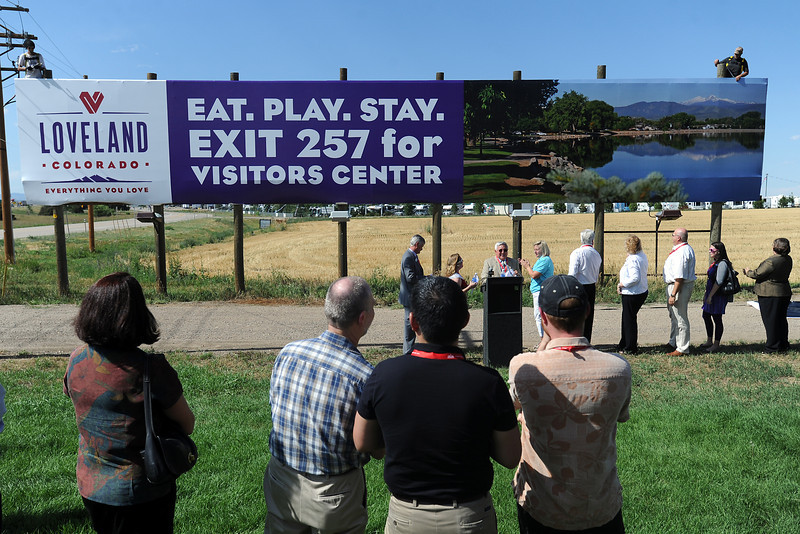 Loveland mayor Cecil Gutierrez, at lectern, speaks during the unveiling of a billboard near the Johnson's Corner RV Retreat that features the city's new brand.