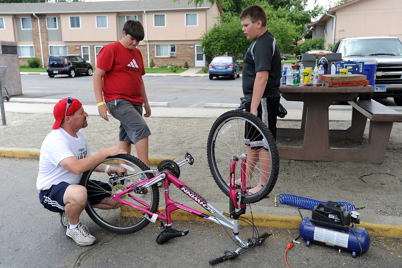 Chase Cook, 13, right, chats with volunteers Bryan Johnson, left, and Owen Montgomery, 13, as they repair bicycles at Maple Terrace Apartments on Thursday, July 12, 2012.