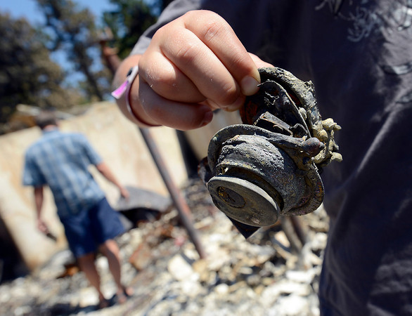 Hunter Squibb, 8, found the charred door lock of his family's home while searching through the rubble.