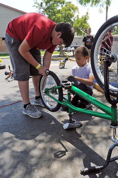 Week of Hope volunteer Owen Montgomery, 13, left, of Rapid City, South Dakota fixes a flat tire on a bicycle while Logan Peckham, 10, looks on at Maple Terrace Apartments on Thursday, July 12, 2012.