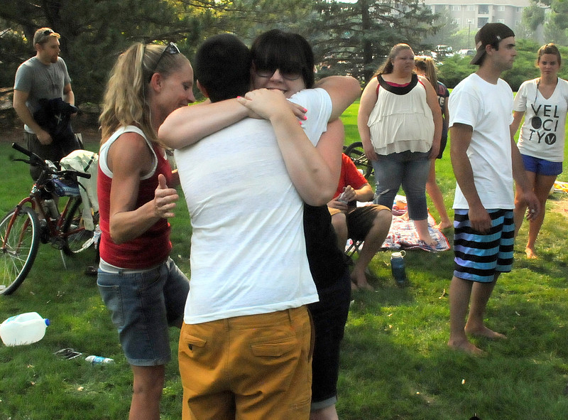 Dylan Tippmann of Loveland, back to camera, gets a goodbye hug from Kauline Sidinger of Denver as some members of a gathering of former youth group members leave their picnic spot at North Lake Park on Wednesday. The group has been coming to the park on the Fourth of July for 14 years.