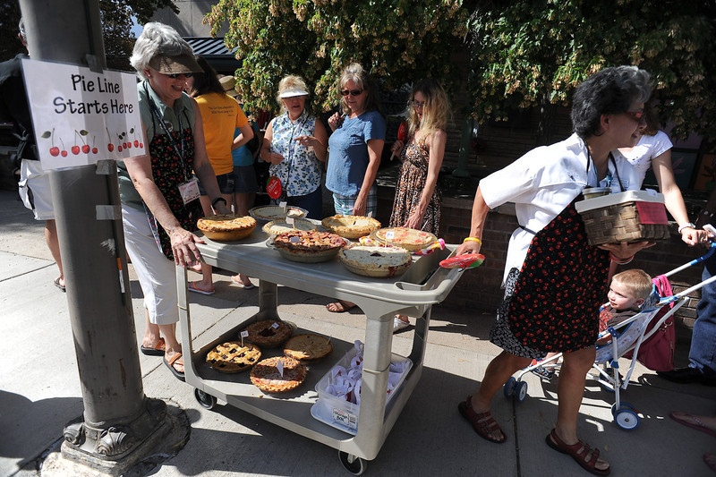Cultural Services board members Kris Ortmann, left, and Juanita Cisneros transport a precious cargo of home-made cherry pies to be judged during the Cherry Pie Celebration at Peters Park on Saturday afternoon.