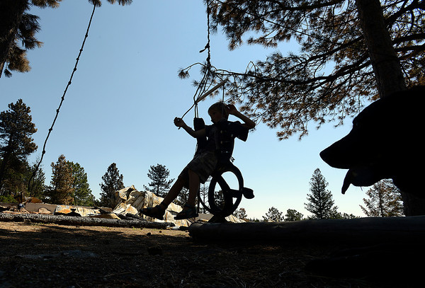 Hunter Squibb, 8, swings on a peice of play equipment that survived the High Park fire with the remains of his family home in the background.