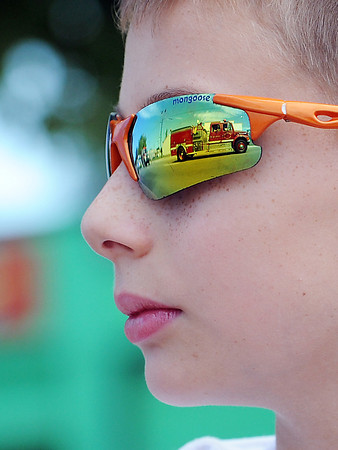 A fire truck is reflected in 11-year-old Kyler Bottke's sunglasses as he watches the Larimer County Fair Parade on Saturday, July 28, 2012 in downtown Loveland.