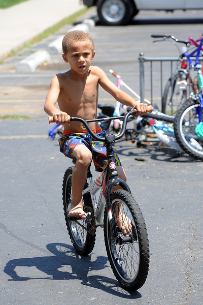 Seven-year-old Michael Peckham rides around on his bike after getting it fixed by volunteers at Maple Terrace Apartments on Thursday, July 12, 2012.
