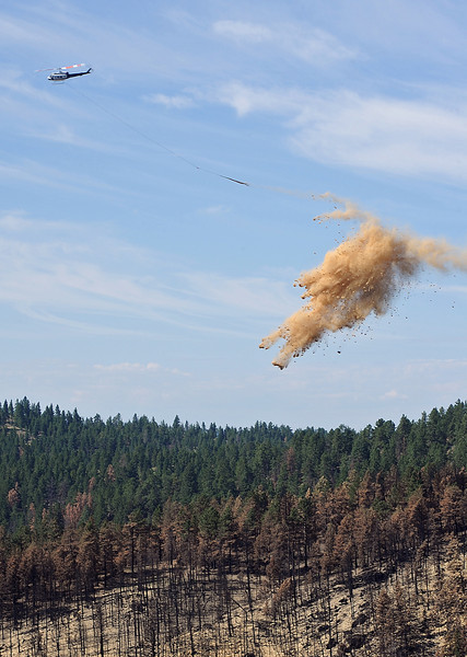 A helicopter drops straw Friday on top of seed that was spread in an area of Soldier Canyon that was burned in the High Park fire near Horsetooth Reservoir. Contractors hired by the Natural Resource Conservation Service dropped seed and straw to stabilize the landscape and prevent ash from polluting the water in Horsetooth Reservoir.